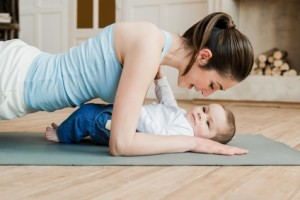 Side view of woman doing plank exercise and spending time with her son at home